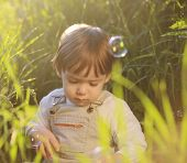 Cute adorable baby kid sitting in beautiful green grass blowing soap bubbles