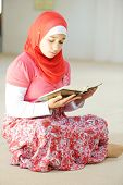 stock photo of muslimah  - Portrait of muslim girl reading Islamic holy book of Koran - JPG