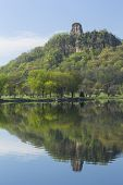 image of winona  - A limestone rock formation on top of a hill with a reflection in a lake - JPG