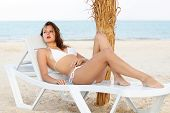 stock photo of leggy  - Pretty leggy woman in white swimsuit lying on the beach bed - JPG