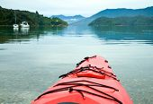 Red touring kayak in waters of the Marlborough Sounds, New Zealand