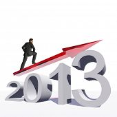 Conceptual 3D human,man or businessman standing over an 2013 year symbol with an arrow isolated on w