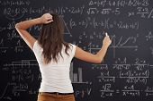 image of scratching head  - Young woman looking at math problem on blackboard - JPG