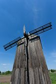 Old wooden windmill on blue sky background