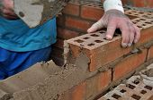 foto of trowel  - A workmne laying bricks in The UK with a trowel - JPG