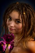 Young Woman With Dreadlocks Against A Dark Background