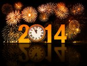 stock photo of firework display  - 2014 year with fireworks and clock displaying 5 minutes before midnight - JPG