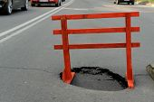 image of traffic signal  - warning sign and a hole on the road - JPG