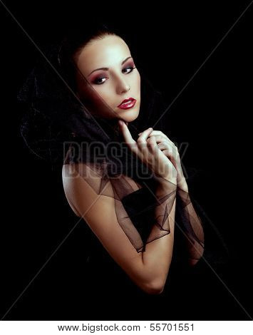 beautiful model posing with black veil, against black studio background