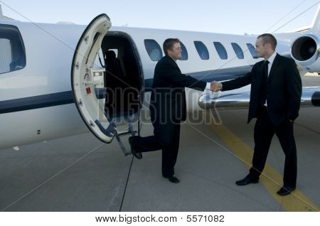 Businessmen Shaking Hands In Front Of Corporate Jet