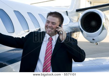 Young Businessman On Cell Phone In Front Of Corporate Jet