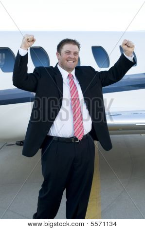Happy Young Businessman In Front Of Corporate Jet