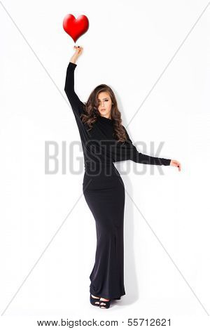 woman in long elegant black dress with red  hart shape above her upraised arm