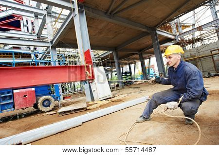 builder worker in uniform at construction site installing metal construction frames
