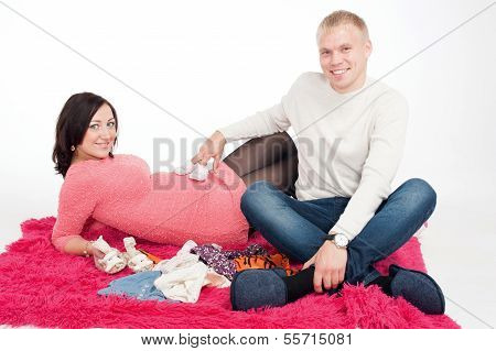 Pregnant Woman And Her Husband With Small Baby Shoes