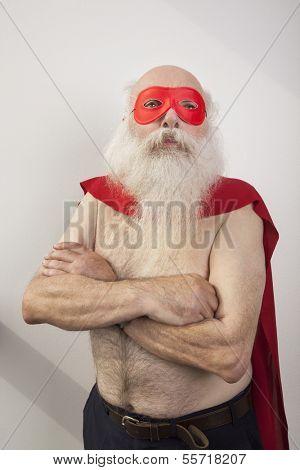 Shirtless senior man in super hero costume against white background