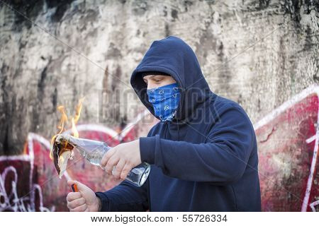 Man with  Molotov cocktail on the wall background