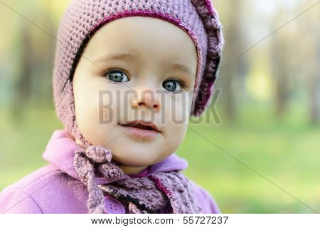 Portrait of cute little girl playing in autumn park. Baby face closeup overnature outdoor.