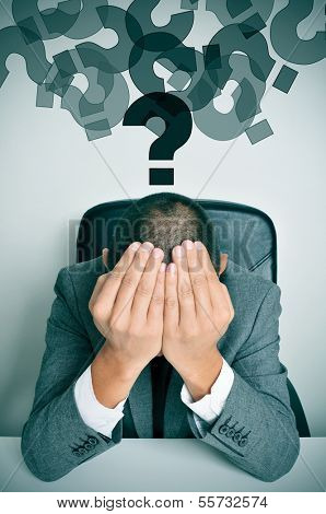 a businessman sitting in a desk with his hands in his head and a cloud of question marks above him