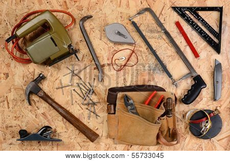 Overhead view of construction equipment and tools laid out on a sheet of plywood. Items include, hammer, nails, square, block plane, saws, tool belt and more. Horizontal format.