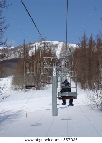 Snowboarder On A Ski Lift