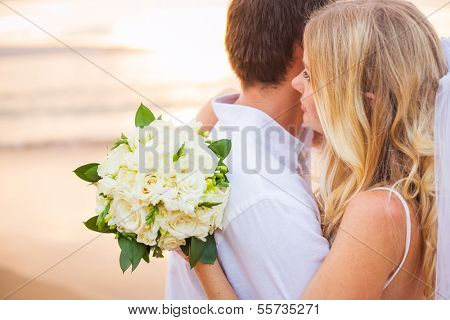 Bride holding bouquet of white flowers gazing at the ocean into the sunset