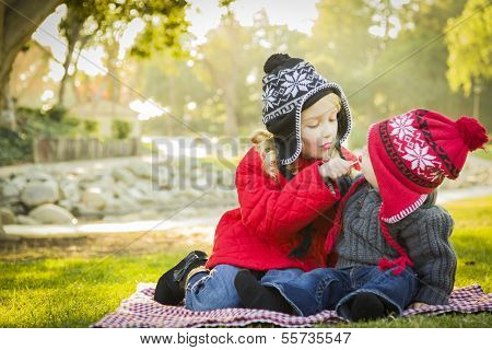 Little Girl with Her Baby Brother Wearing Winter Coats and Hats Sharing a Lollipop Outdoors at the Park.