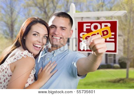 Mixed Race Excited Military Couple In Front of New Home with New House Keys and Sold Real Estate Sign Outside.