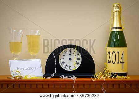 A clock showing midnight at New Year with a bottle of champagne labelled 2014, glasses and invitation surrounded by streamers.