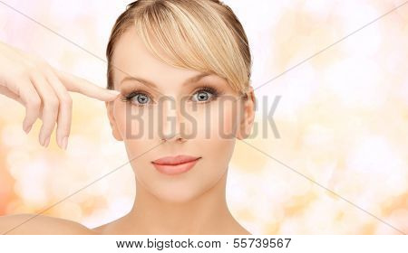health, spa and beauty concept - face of beautiful woman touching her eye area