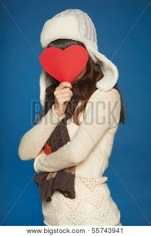 Winter girl holding heart shape in front of face