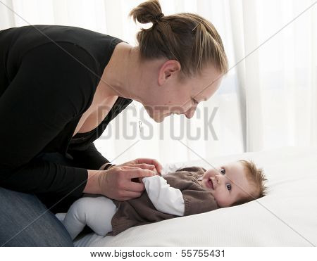 Young Mother Playing With Sweet Baby Girl