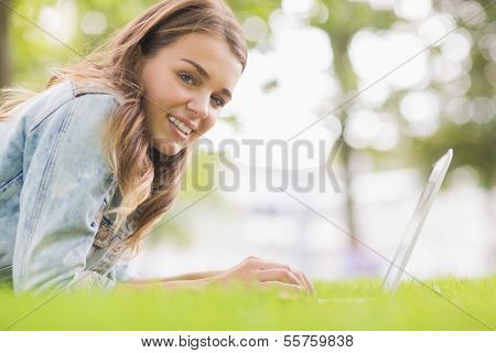 Happy student lying on the grass using her laptop looking at camera on college campus
