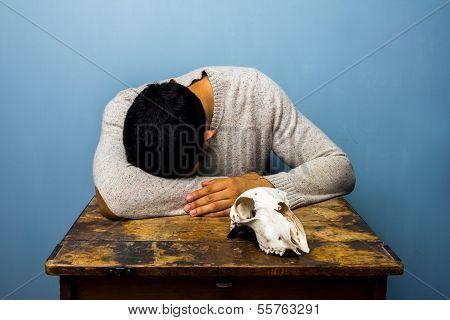 Sad Man With Skull At Desk