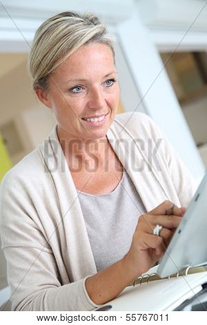 Businesswoman working from home with tablet