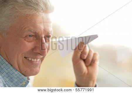 Senior man with paper plane