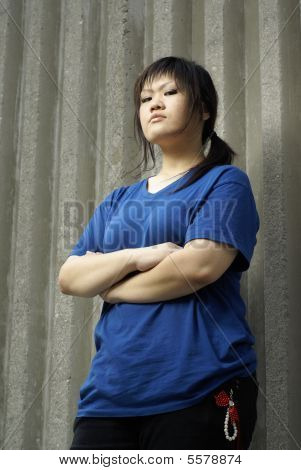 Asian teen girl leaning against wall