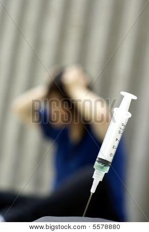 Syringe and female addict in anguish