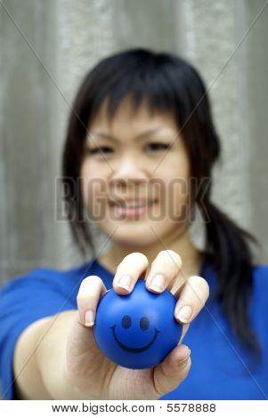 Young asian woman in blue holding smiley ball