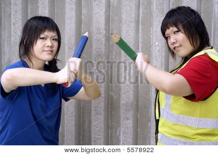 Two asian teen girls with large pencils