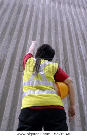 Asian contractor pointing upwards