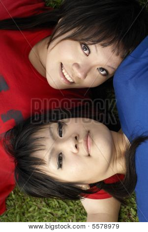 Two happy asian teen girls portrait on grass