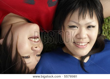 Two happy asian teen girls lying on grass