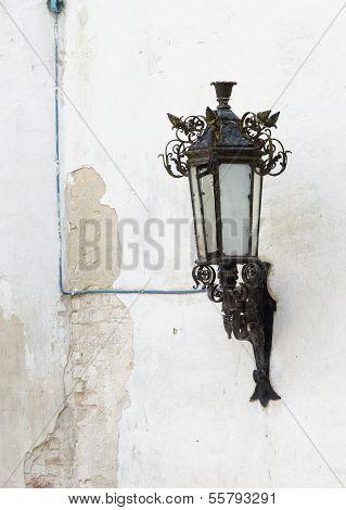 Retro street lantern on peeling plaster wall