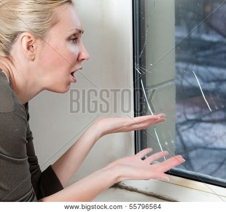 The sad young woman near a window with the burst broken glass
