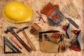 Overhead view of construction equipment and tools laid out on a sheet of plywood. Items include, har