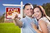 stock photo of arms race  - Mixed Race Excited Military Couple In Front of New Home with New House Keys and Sold Real Estate Sign Outside - JPG