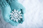 stock photo of knitting  - Female hands in light teal knitted mittens with sparkling wonderful snowflake on a white snow background - JPG