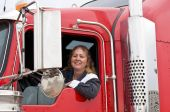 stock photo of big-rig  - Woman truck driver leaning out the drivers side window - JPG