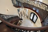 stock photo of stairway  - Curved stairway leading down into foyer in luxury home - JPG